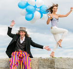 Man on stilts and woman with balloons
