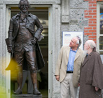 Men speaking beside statue