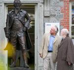 Men speaking beside statue